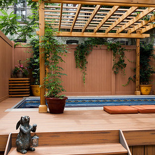 This is an example of a medium sized vintage back rectangular above ground swimming pool in New York with a pool house and decking.