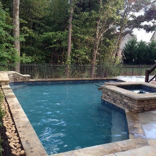 Immagine di una piccola piscina american style personalizzata dietro casa con una vasca idromassaggio e pedane