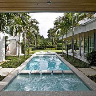 Ejemplo de piscina moderna, rectangular, en patio, con losas de hormigón