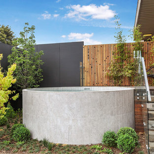 Design ideas for a mid-sized contemporary backyard round aboveground pool in Melbourne with decking.