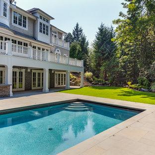 Esempio di una grande piscina monocorsia vittoriana rettangolare dietro casa con una vasca idromassaggio e pavimentazioni in pietra naturale