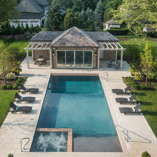 This is an example of a mid-sized traditional backyard rectangular lap pool in Chicago with a hot tub and natural stone pavers.