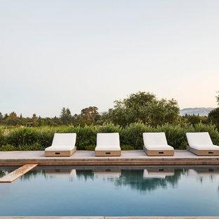 Imagen de piscinas y jacuzzis alargados, de estilo de casa de campo, de tamaño medio, rectangulares, en patio trasero, con adoquines de hormigón