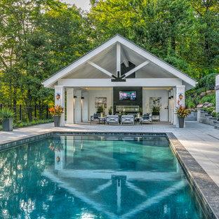 Modelo de casa de la piscina y piscina alargada, clásica renovada, grande, rectangular, en patio trasero, con adoquines de hormigón