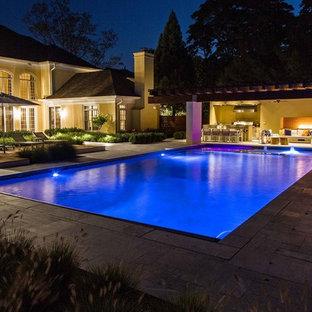 Imagen de casa de la piscina y piscina natural, minimalista, grande, rectangular, en patio trasero, con adoquines de piedra natural