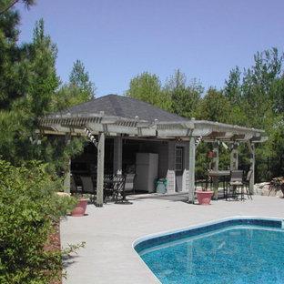 Ejemplo de casa de la piscina y piscina contemporánea, de tamaño medio, en forma de L, en patio lateral, con losas de hormigón