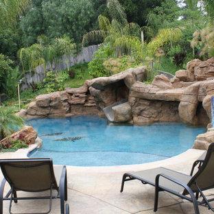 Idee per una grande piscina naturale tropicale personalizzata dietro casa con un acquascivolo e cemento stampato