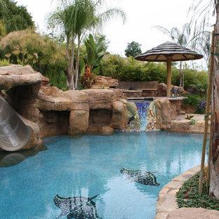 ロサンゼルスの大きいオーダーメイドトロピカルスタイルのおしゃれなプール (ウォータースライダー、天然石敷き) の写真