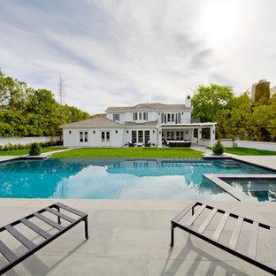 Imagen de piscinas y jacuzzis infinitos, minimalistas, extra grandes, rectangulares, en patio trasero, con losas de hormigón