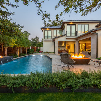 Example of a large trendy backyard concrete and rectangular lap pool fountain design in Dallas