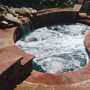 Imagen de piscinas y jacuzzis alargados, tradicionales, de tamaño medio, tipo riñón, en patio trasero, con losas de hormigón