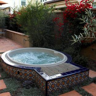 Modelo de piscinas y jacuzzis mediterráneos, de tamaño medio, redondeados, en patio trasero, con suelo de baldosas