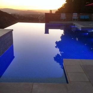 Ejemplo de piscinas y jacuzzis infinitos, contemporáneos, grandes, rectangulares, en patio trasero, con adoquines de hormigón