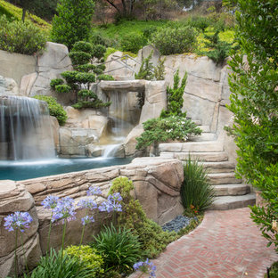 Photo of an eclectic natural pool in Austin with a water feature.