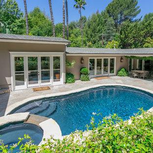 Ejemplo de piscinas y jacuzzis naturales, contemporáneos, de tamaño medio, tipo riñón, en patio trasero, con adoquines de piedra natural
