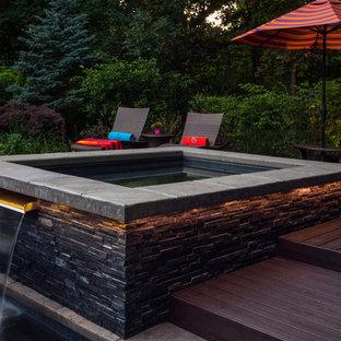 Esempio di una grande piscina contemporanea dietro casa con fontane e pedane
