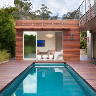 Diseño de casa de la piscina y piscina alargada, actual, de tamaño medio, rectangular, en patio trasero, con entablado