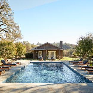 Пример оригинального дизайна: спортивный, прямоугольный бассейн на заднем дворе в стиле кантри с домиком у бассейна и покрытием из плитки
