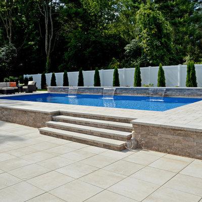 Elegant backyard brick and custom-shaped aboveground pool photo in New York