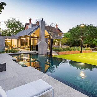 Large contemporary backyard rectangular infinity pool in Melbourne with a hot tub.