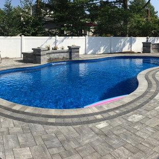 Ejemplo de piscina con fuente natural, costera, grande, a medida, en patio trasero, con adoquines de hormigón