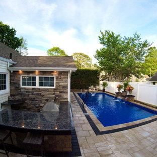 Foto de piscina alargada, contemporánea, grande, rectangular, en patio trasero, con adoquines de hormigón