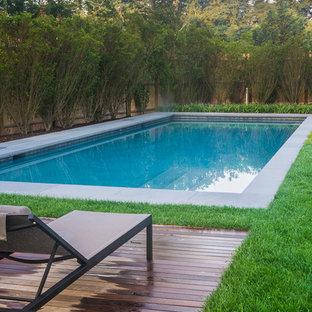 Foto di una piscina minimalista rettangolare di medie dimensioni e dietro casa con una dépendance a bordo piscina e pedane