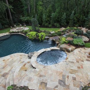 """Immagine di una grande piscina naturale classica a """"C"""" dietro casa con una vasca idromassaggio e pavimentazioni in pietra naturale"""