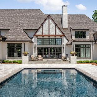 Ejemplo de piscinas y jacuzzis de estilo de casa de campo, grandes, rectangulares, en patio trasero, con suelo de baldosas