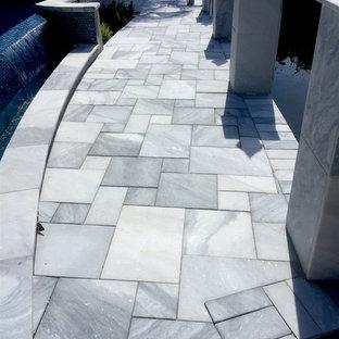 タンパの広い長方形モダンスタイルのおしゃれなプール (天然石敷き) の写真