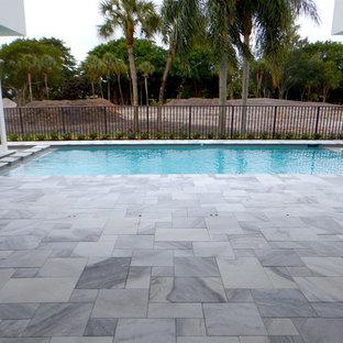 Esempio di una grande piscina monocorsia moderna rettangolare dietro casa con pavimentazioni in pietra naturale