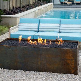 Imagen de piscina con fuente actual, de tamaño medio, rectangular, en patio trasero, con gravilla