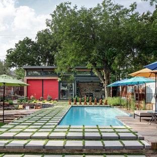 Exemple d'une piscine arrière industrielle en L avec des pavés en béton.