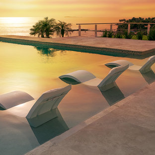 Imagen de piscina infinita, moderna, grande, a medida, en patio trasero, con suelo de baldosas