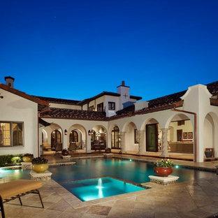 Foto de piscinas y jacuzzis alargados, mediterráneos, grandes, en forma de L, en patio trasero, con suelo de baldosas