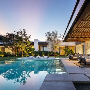 Inspiration för mycket stora moderna anpassad pooler på baksidan av huset, med betongplatta