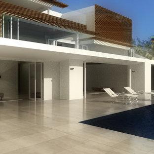 Modelo de piscina infinita, actual, grande, rectangular, en patio trasero, con privacidad y adoquines de piedra natural