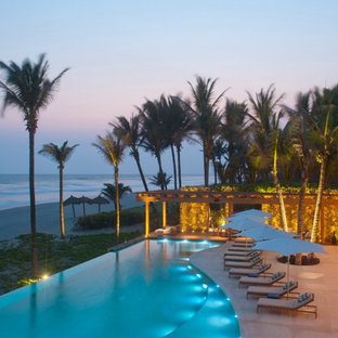 Inspiration for an expansive tropical custom-shaped infinity pool in Other.