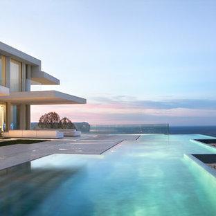 Diseño de piscina infinita, actual, extra grande, a medida, en patio trasero, con losas de hormigón