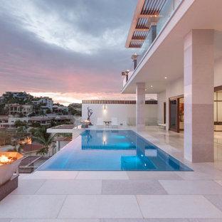 Modelo de piscina infinita, contemporánea, grande, rectangular, en patio, con privacidad y adoquines de piedra natural