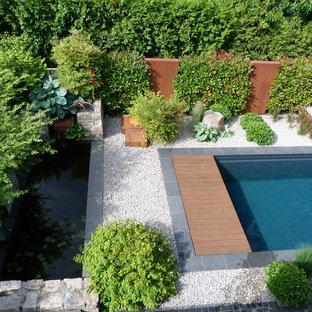 Foto de piscina alargada, moderna, de tamaño medio, rectangular, en patio trasero, con granito descompuesto