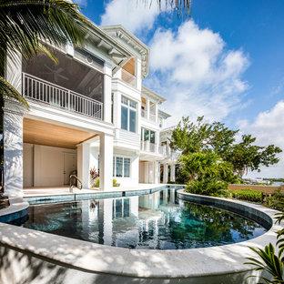 Mid-sized coastal backyard stone and custom-shaped natural pool photo in Tampa