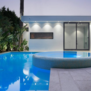 This is an example of a large modern backyard rectangular lap pool in Melbourne with a hot tub and natural stone pavers.