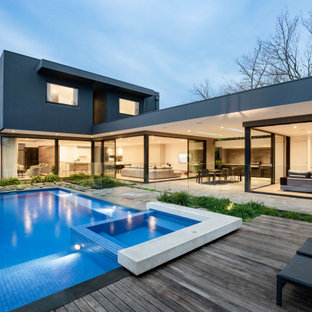 Contemporary backyard rectangular pool in Melbourne with a hot tub and decking.