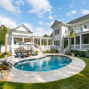 Modelo de piscina costera, tipo riñón, en patio trasero, con adoquines de piedra natural