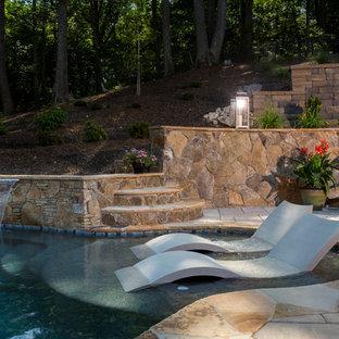 Ejemplo de piscina con fuente actual, grande, a medida, en patio trasero, con adoquines de piedra natural