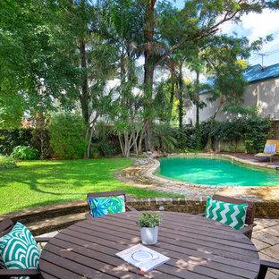 Modelo de piscina alargada, ecléctica, grande, tipo riñón, en patio trasero, con adoquines de ladrillo