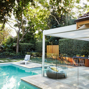 This is an example of a mid-sized contemporary backyard custom-shaped pool in Sydney with natural stone pavers.