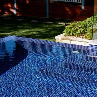 Esempio di una grande piscina fuori terra etnica rettangolare dietro casa con pedane