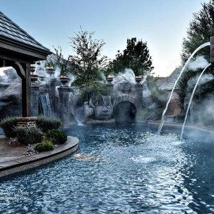 Ejemplo de piscina con tobogán natural, vintage, grande, redondeada, en patio trasero